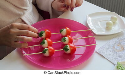 A woman decorates parsley with boiled quail eggs and tomato...