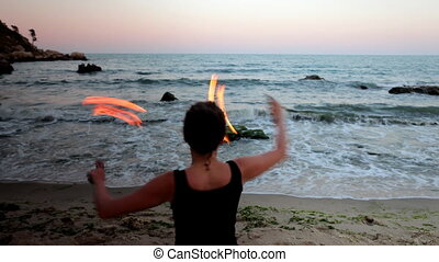 a woman does a fire performance on the beach