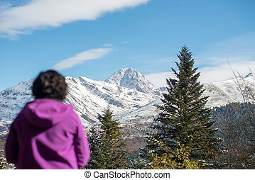 woman dressed in purple looking at the snowy mountain