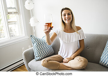 Woman drinking beer sitting on a couch in the living room at home