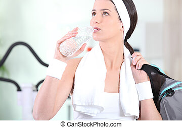 a woman drinking water after fitness