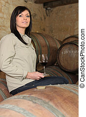 a woman drinking wine in a cellar
