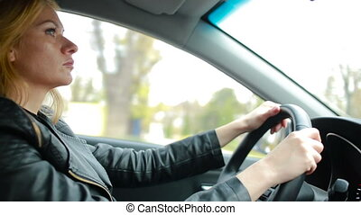 A woman driving a car. attentive girl rides around city -...