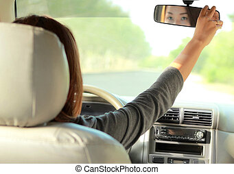 a woman driving a car while adjusting the rearview mirror
