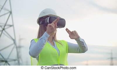 A woman electrician in virtual reality glasses moves her...