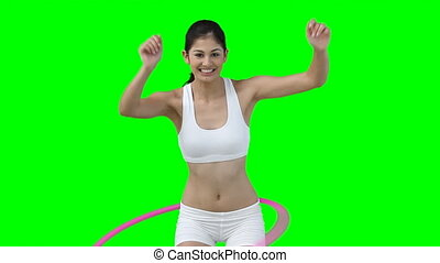 A woman enjoys using a hula hoop against a green background