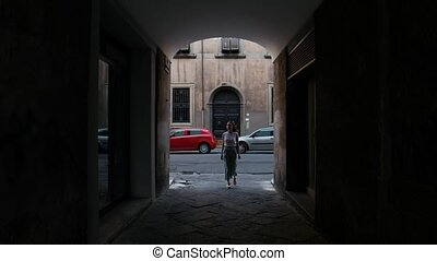 A woman enters a dark alley and goes ahead. Mid shot