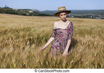 a woman farmer in a field of ripe wheat and rye