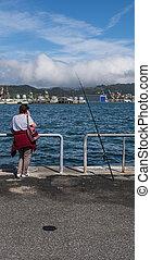 a woman fishing in the gulf of la spezia