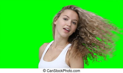 A woman flicking back her hair and posing