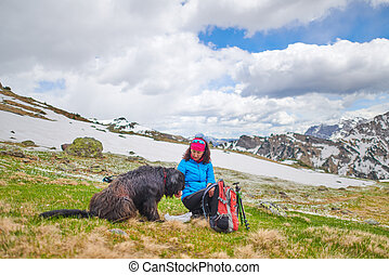 A woman from food to her dog during a walk in the mountains