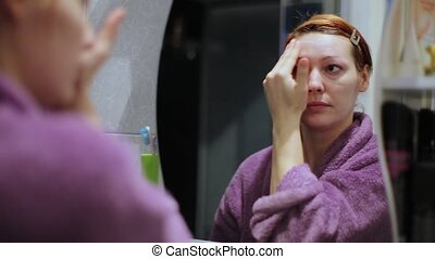 A Woman Gets A Moisturizer Cream On Her Face