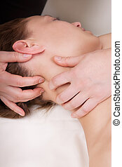 A woman getting a stress relieving pressure point massage on her neck by a health therapist