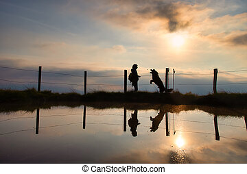 A woman gives a cookie to her dog during a walk in the mountains at sunset