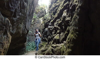 A woman goes into a narrow cleft in the mountains.