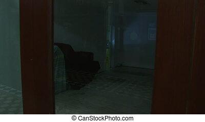 A woman going inside an office with a flashlight - A medium...