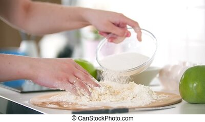 A woman hand adding flour to the dough and continue kneading it. Mid shot