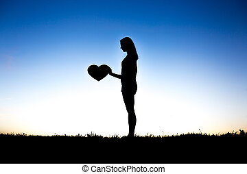 woman hands holding hearts silhouette on Silhouette sunset