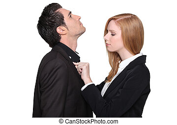 a woman helping a man to dress his shirt