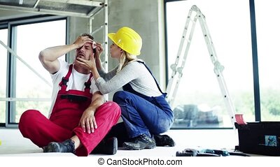 A woman helping man worker after an accident at the construction site.