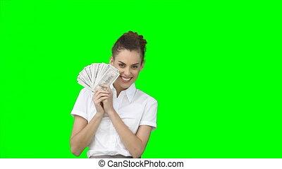 A woman hiding her face behind a fan of money