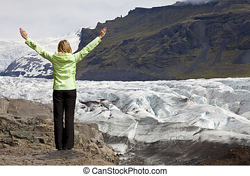 A woman hiker arms raised celebrating by the Vatnajokull Glacier, Iceland