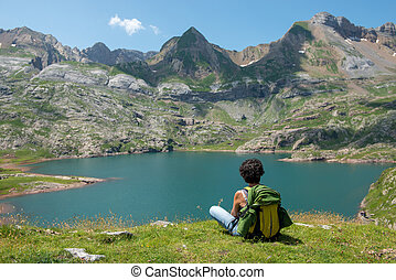 woman hiker resting and looking at lake in the Pyrenees mountains