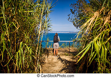 A woman hiker with a backpacker in a reeds path looking the sea