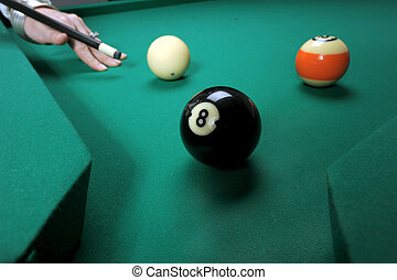 A woman hits balls on a pool (billard) table during play