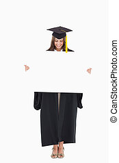 A woman holding a blank sheet in front of her and she looks down at it while smiling