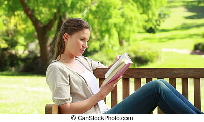 A woman holding a book while sitting on a bench