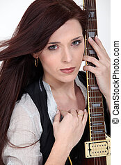 A woman holding a guitar.