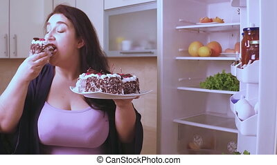 A woman holding a piece of cake on a table