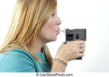 a woman holding a police breath test as she blows into it.
