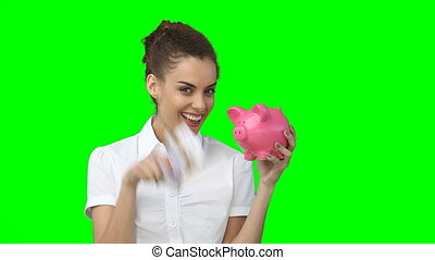 A woman holding up a piggy-bank and a fan of cash as she smiles