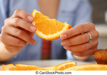 A woman holds a slice of sliced orange