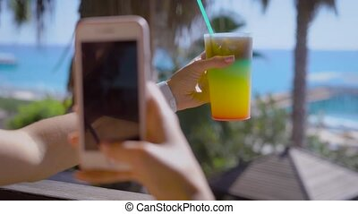 A woman holds an alcoholic cocktail in her hand with a different color and photographs it on her mobile phone, the lady is on vacation