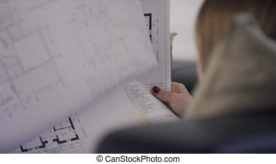 A woman holds in her hands a sheet of paper with an apartment layout.