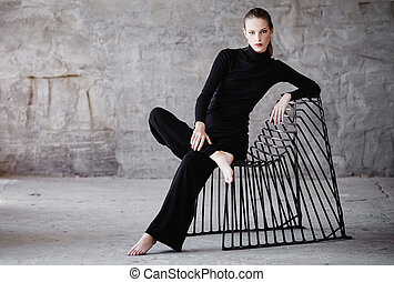 A woman in a black clothes sitting on a chair.