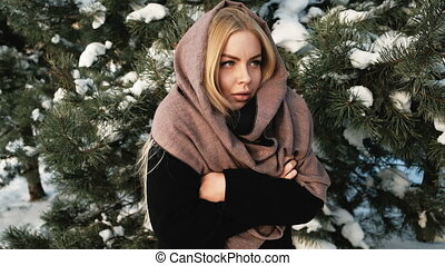 A woman in a black coat and scarf freezing in the winter forest