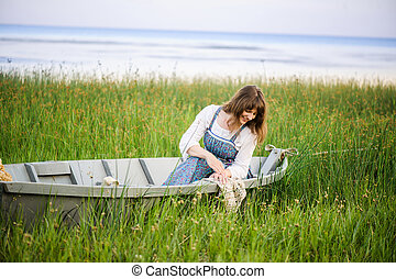 a woman in a boat on the shore