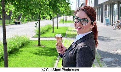 A woman in a business suit turns around and eats a vanilla ice cream cone outdoors