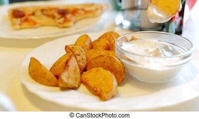 A woman in a cafe is eating fried potatoes with sauce