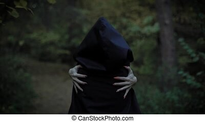 a woman in a cloak with a hood embraces herself behind her...