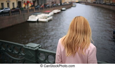 A woman in a coat stands on a bridge and looks down at the...