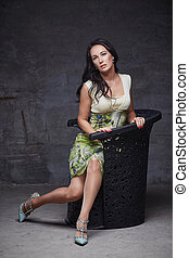 A woman in a dress sitting on the chair.