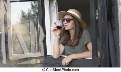 A woman in a hat looks out of the window with a glass of red wine