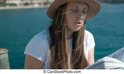 A woman in a hat reads a book aloud, and her hair croaks from the wind