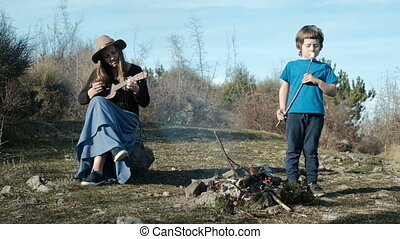 A woman in a hat with a guitar sits by the fire next to the child.