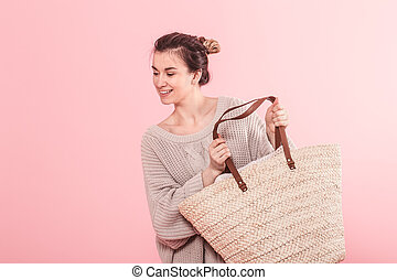 A woman in a knitted sweater holding a wicker basket with clothes